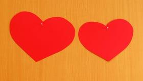 Dos corazones clavados a la tarjeta Foto de archivo