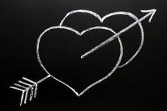 Dos corazones con la flecha del Cupid que golpea a través Fotos de archivo libres de regalías