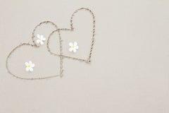 Dos corazones con las flores blancas en el fondo de la superficie de la playa Foto de archivo