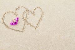 Dos corazones con las flores rosadas en el fondo de la superficie de la playa Foto de archivo