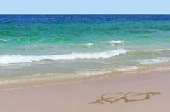 Dos corazones con una flecha dibujada en la arena en la playa Concepto del amor Foto de archivo libre de regalías