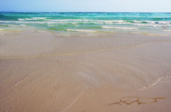 Dos corazones con una flecha dibujada en la arena en la playa Concepto del amor Fotografía de archivo libre de regalías