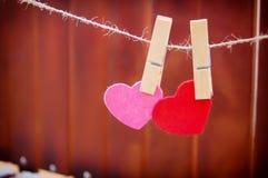 Dos corazones cuelgan en clothesboards en un fondo de madera imagen de archivo