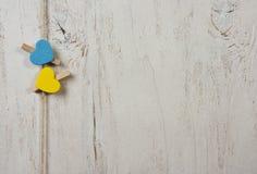 Dos corazones de azul y de amarillo en un fondo blanco viejo Fotografía de archivo