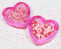Dos corazones de cristal rosados con la tarjeta del día de San Valentín asperjan Fotografía de archivo libre de regalías
