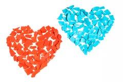 Dos corazones de la tarjeta del día de San Valentín de pedazos rasgados de papel rojo y azul Imagenes de archivo