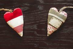 Dos corazones de la tela en la tabla de madera el día del ` s de la tarjeta del día de San Valentín Foto de archivo