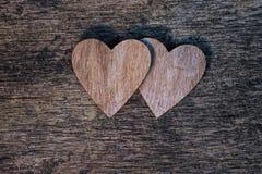 Dos corazones de madera en el fondo de madera de la textura fotografía de archivo libre de regalías