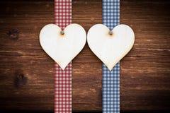 Dos corazones de madera en tablones de madera oscuros Fotografía de archivo