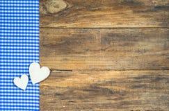 Dos corazones de madera en tela a cuadros azul Foto de archivo libre de regalías