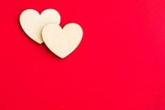 Dos corazones de madera en un fondo rojo brillante Fotos de archivo libres de regalías