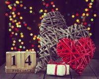 Dos corazones de madera y un calendario con una fecha el 14 de febrero en una tabla oscura Día del `s de la tarjeta del día de Sa Foto de archivo