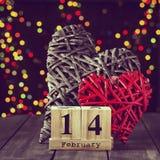 Dos corazones de madera y un calendario con una fecha el 14 de febrero en una tabla oscura Día del `s de la tarjeta del día de Sa Imagen de archivo libre de regalías