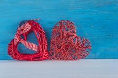 Dos corazones de mimbre rojos en fondo rústico azul Foto de archivo libre de regalías