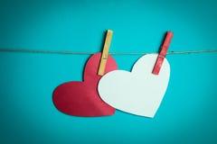 Dos corazones de papel atados a una cuerda con los pernos rojos Foto de archivo