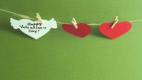 Dos corazones de papel rojos y un corazón blanco con la enhorabuena y las alas fijadas con las pinzas en un cordón en verde almacen de video