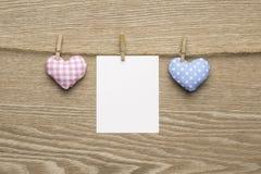 Dos corazones del amor con las fotos inmediatas en blanco sobre fondo de madera Imagenes de archivo