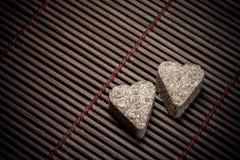Dos corazones del azúcar en textura de madera Fotografía de archivo libre de regalías