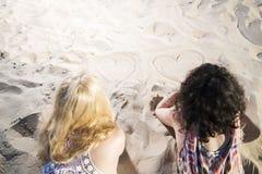 Dos corazones del drenaje de la mujer joven en la arena. Imágenes de archivo libres de regalías