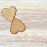 Dos corazones del pan de jengibre en un tablero de madera Foto de archivo libre de regalías