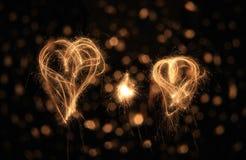 Dos corazones del sparkler en la noche fotos de archivo