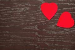 Dos corazones del terciopelo en un tablero de madera el día del ` s de la tarjeta del día de San Valentín Imagenes de archivo