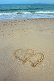 Dos corazones dibujados en arena Foto de archivo libre de regalías