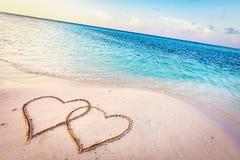 Dos corazones dibujados en la arena de una playa tropical en la puesta del sol fotos de archivo