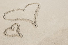 Dos corazones drenados en arena Foto de archivo libre de regalías