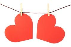 Dos corazones en la cuerda para tender la ropa. Aislado. Val Imagenes de archivo