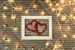 Dos corazones en marco de la foto sobre la tela escocesa con las luces, la comodidad y el concepto romántico con historia fotografía de archivo libre de regalías