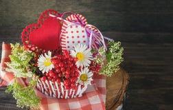 Dos corazones en una cesta de mimbre con las bayas y las flores el día del ` s de la tarjeta del día de San Valentín en un estilo Imagen de archivo libre de regalías
