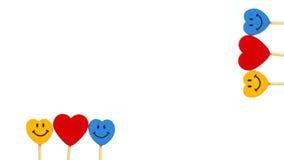Dos corazones entre dos caras de la sonrisa en el fondo blanco Fotografía de archivo
