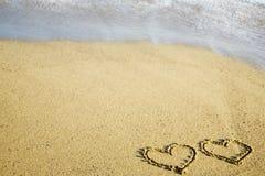 Dos corazones escritos en la arena Fotos de archivo libres de regalías