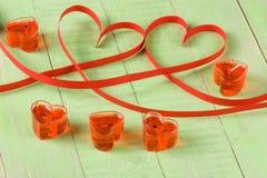 Dos corazones hechos de cinta de papel roja con las velas aisladas en el fondo blanco Fotografía de archivo