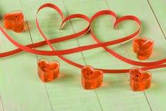 Dos corazones hechos de cinta de papel roja con las velas aisladas en el fondo blanco Fotos de archivo libres de regalías
