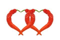 Dos corazones integrados por las pimientas de chile rojo Fotos de archivo libres de regalías