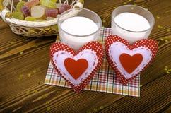 Dos corazones, mermelada en una cesta de mimbre y dos vidrios de leche Imagen de archivo libre de regalías