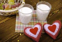Dos corazones, mermelada en una cesta de mimbre y dos vidrios de leche Imágenes de archivo libres de regalías
