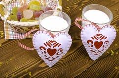 Dos corazones, mermelada en una cesta de mimbre y dos vidrios de leche Foto de archivo libre de regalías