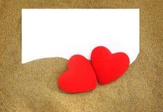 Dos corazones rojos con la tarjeta en blanco Foto de archivo libre de regalías