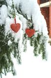 Dos corazones rojos de la materia textil que cuelgan en rama nevosa pesada del abeto, cerca de casa del ladrillo rojo Feliz Navid foto de archivo libre de regalías
