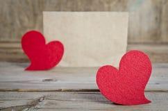 Dos corazones rojos de la tela en un tablero de madera Foto de archivo libre de regalías