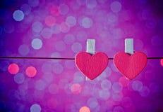 Dos corazones rojos decorativos que cuelgan contra el fondo ligero azul y violeta del bokeh, concepto de día de San Valentín Foto de archivo