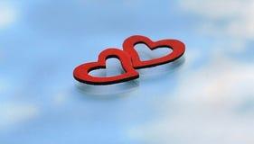 Dos corazones rojos en el fondo de la reflexión del cielo Imágenes de archivo libres de regalías