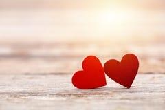 Dos corazones rojos en fondo de madera en puesta del sol Imagen de archivo