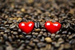 Dos corazones rojos en granos de café Fotos de archivo