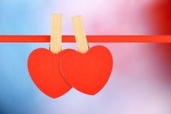 Dos corazones rojos en la cinta en fondo multicolor Imágenes de archivo libres de regalías