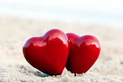 Dos corazones rojos en la playa. Amor imagenes de archivo