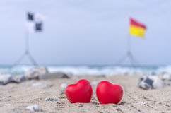 Dos corazones rojos en la playa con las banderas de la resaca en el fondo Fotografía de archivo libre de regalías